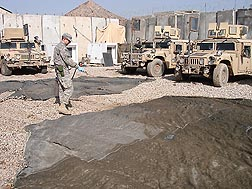 At a remote patrol base in Iraq, ARS scientist and U.S. Army medical entomologist Seth Britch applies a residual treatment of lambdacyhalothrin to camouflage netting and shade cloth that will be suspended over outdoor eating and cooking areas and over areas in between dormitories: Click here for full photo caption.