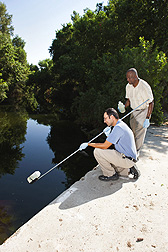 Technician Damon Baptista (left) and microbiologist Mark Ibekwe collect a water sample from a creek that drains into the middle Santa Ana River Watershed: Click here for full photo caption.