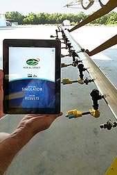 Photo: A computer  tablet (being held in front of a spray boom) displays a new aerial spray app. Link to photo information