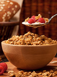 Photo:  A spoon of cereal, raspberries and milk is being held above a bowl of cereal. Link to photo information