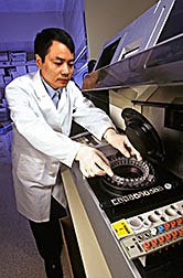 Guohua Cao loads extracts of fruit and vegetable samples onto an automated centrifugal analyzer.