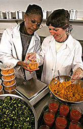 Dietitian Evelyn Lashley (left) and food service worker Sara Mayock weigh kale, tomato juice, and sweetpotaotes for a carotenoid study.