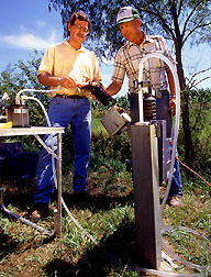 In a small watershed in Iowa, hydrologist Michael Burkart (left) and a farmer draw from a 30-foot-deep sampling well to test for herbicides and nitrate. Click the image for additional information about it.