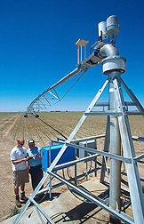 A research leader downloads data about the movement of a center-pivot irrigation system. Click here for full photo caption.