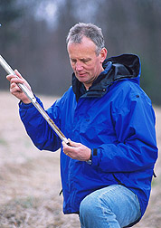 Photo: Sharpley collects a soil sample from a test plot. Link to photo information