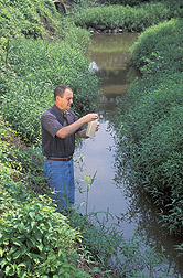 Soil scientist handles a water sample: Click here for full photo caption.
