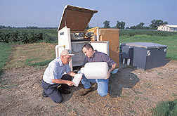 Agricultural engineer and soil scientist collect runoff water samples: Click here for full photo caption.