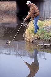 Technician collects a water sample: Click here for full photo caption.
