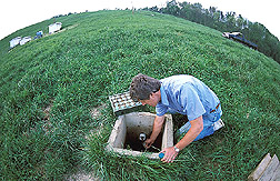 Soil scientist collects a water sample for carbon analysis: Click here for full photo caption.
