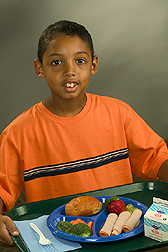 Student holds a tray displaying a healthy school meal: Click here for full photo caption.