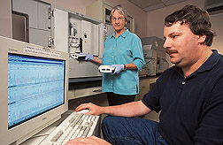 Sharon Horn and  William Miller prepare samples of Campylobacter for DNA analysis. Monitor shows sequence of  DNA sample run earlier. Link to photo information