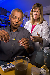 Chemist (right) demonstrates the simple, rapid enzymatic mannitol test to a factory laboratory technician at Alma Sugarcane Factory, Lakeland, Louisiana: Click here for full photo caption.