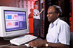 Plant physiologist (foreground) uses the GLYCIM computer model to simulate soybean growth while soil scientist checks instruments that control conditions and monitor the plants inside growth chambers: Click here for full photo caption.