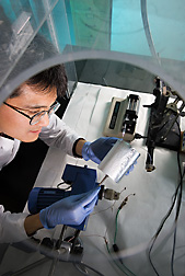Chemist examines a film made from nanofibers after electrospinning on aluminum foil: Click here for full photo caption.
