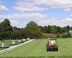 Pesticides being applied to experimental turf plots maintained at a golf course fairway: Click here for full photo caption.