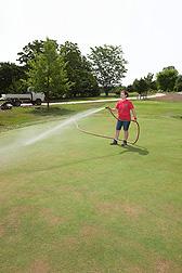 Grass Roots intern Megan Wiemer waters the golf green exhibit.