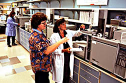 Technicians Kathryn Morford (left foreground) and Ronah Grigg analyze extracts of crops grown on IR-4 test plots