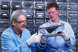 Virologist and food scientist examine mice used in studies: Click here for full photo caption.
