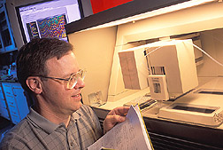 Chemist Tim Smith observes an automated DNA sequence instrument.