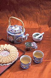 Tea kettle, tea leaves, two cups of tea, and cookies: Click here for full photo caption.
