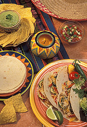 A Mexican meal featuring tacos made with soft white flour tortillas. Link to photo information
