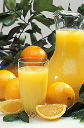 Photo: A pitcher and glass of fresh squeezed orange juice beside some fresh oranges.