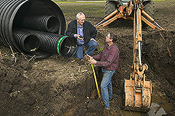 Soil scientist discusses site conditions for a drainage water management and recycling structure with drainage contractor: Click here for full photo caption.
