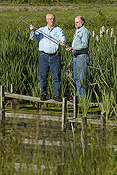 Soil scientist and Ohio State University extension agricultural engineer discuss features and treatment efficiency of a constructed wetland: Click here for full photo caption.