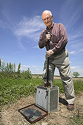 Soil scientist moves a flashboard riser in a drainage water management structure: Click here for full photo caption.