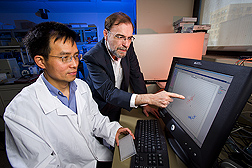 Chao Qiang Lai and Jose Ordovas view computer screen displaying DNA data. Link to photo information