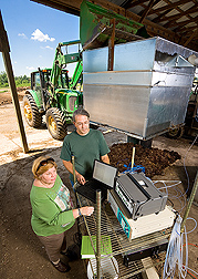 Microbiologist and soil scientist review gas-emission data from an enclosed compost pile: Click here for full photo caption.