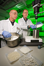 Food technologist (left) and plant physiologist prepare batches of starch-based dough which will be further processed by extrusion to form heat-expandable pellets: Click here for full photo caption.