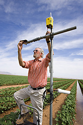 Physical scientist aligns ARS-designed radiometers for monitoring cotton growth: Click here for full photo caption.