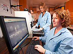 Geneticist (right) and technician use a gel imager to evaluate genotypes of Red Angus cattle for osteopetrosis phenotypes: Click here for full photo caption.