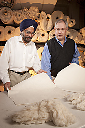 Cotton technologist (left) and research leader examine needled-punched nonwoven products made with classical raw (greige) cotton and precleaned raw cotton, respectively: Click here for full photo caption.