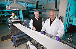 Technicians and research leader apply a new treatment to a hydroentangled greige cotton nonwoven fabric on the Mathis laboratory equipment: Click here for full photo caption.