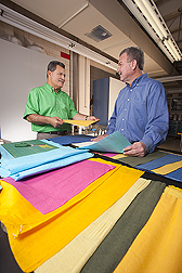Technician (left) and textile chemist discuss new uses for the colorful cotton-based nonwoven fabrics they dyed and finished in the wet-finishing laboratory: Click here for full photo caption.