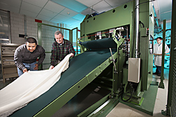 Technician (left) and textile chemist (center) examine a cross-lapped web (batt) as they prepare to feed it into the needle-punch machine to produce a fabric containing mostly cotton. Another technician waits for the fabric on the exit side: Click here for full photo caption.