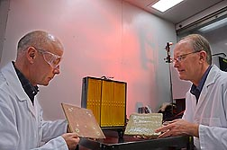 Food technologist Artur Klamczynski (left) and plant physiologist Greg Glenn prepare to use an infrared heater, located behind them, to conduct burn tests of siding coated with experimental fire-retardant gel: Click here for full photo caption.