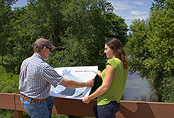 Photo: Two scientists reviewing a map standing in front of Beaver Creek. Link to photo information