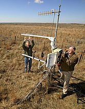 Jim Bradford and Phillip Sims adjust a weather station fitted with instruments that measure carbon cycling. Link to photo information