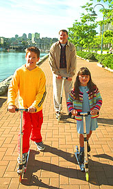 Boy, girl and man riding scooters.