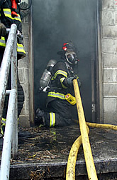 Firefighter in doorway of smoke-filled building (training exercise).