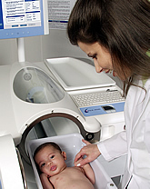 Woman in lab coat looks at infant in Pea Pod chamber tray.