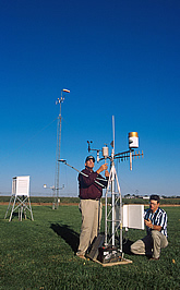Researchers check and adjust the equipment at a field weather station. Link to photo information