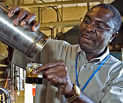 Akwasi Boateng pours bio-oil from a canister.