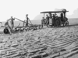Several men congregate by a tractor-pulled one-way production plow in a partially tilled field.