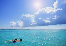 Two people snorkeling under bright sunlight.