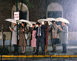 Photo: Rain falling on an urban street and people standing at a bus stop.