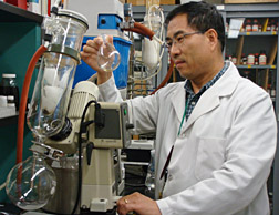 Photo: ARS chemist Aijun Zhang examining flask.